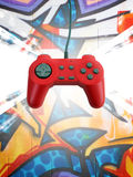 Game controller w clipping path. A red game controller over a graffiti background.  This file includes the clipping path for the controller Stock Photography