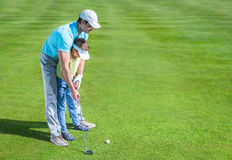 Game. Dad and son playing golf Stock Images