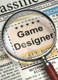Game Designer Hiring Now. 3D. Game Designer - CloseUp View Of A Classifieds Through Loupe. Game Designer - Close View of Small Advertising in Newspaper with Stock Photo