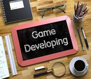 Game Developing - Text on Small Chalkboard. 3d Stock Photography