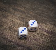 Game dice number three. On the wooden table Stock Photography