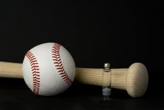 Game essentials. A suggestive photo of steroid use in baseball with a bat, ball, and steroid vial Royalty Free Stock Photo