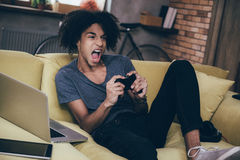 This game is so exciting!. Excited young African man playing video game and keeping his mouth open while sitting on the couch at home Stock Image