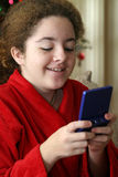 Game Girl. A young girl playing a handheld game with a Christmas tree in the background royalty free stock photos