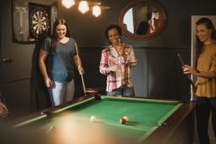 Game on Girls. Small group of female friends playing a game of pool in a games room in a house stock photo