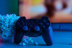 Game joystick from the console or PC with a bowl of popcorn on the background of a TV or monitor. With blue and red color light. stock photos