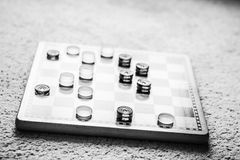 The Game of Kings and Pawns. Black and white picture of a game of checkers with a lot of kings on the board Stock Photo