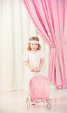 Game. Little beautiful girl play with pram Royalty Free Stock Photos
