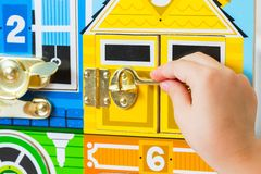 A game with locks. The child opens the locks. Busy-board for For children. Children`s educational toys. Royalty Free Stock Images