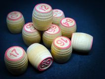 Game of lotto barrels with numbers. A pile of numbered wooden barrels for game of lotto, on rough black background Stock Image
