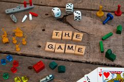 `The Game` made from Scrabble game letters. Risk, Battleship pieces, Monopoly, Settler of Catan and other game pieces royalty free stock photos
