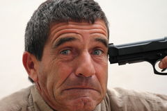 Game or madness?. Fear expression of a man with a gun on his temple Stock Photo