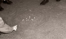 Game of marbles. Schoolboys playing marbles popular years ago Royalty Free Stock Images
