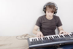 Game on a MIDI-keyboard. Game process on a MIDI-keyboard, man in headphones Stock Photography