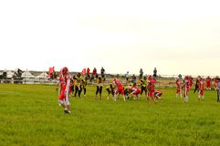 American football. Game moment in the match between amateur teams on the green platform of the festival. stock photo