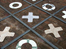 Game - naughts and crosses. Naughts and Crosses / tic tac toe game on ground stock photo