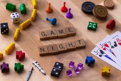 `Game Night` made from Scrabble game letters. Risk, Battleship pieces, Monopoly, Settler of Catan and other game pieces royalty free stock photography