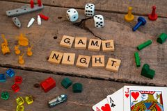 `Game Night` made from Scrabble game letters. Risk, Battleship pieces, Monopoly, Settler of Catan and other game pieces royalty free stock image
