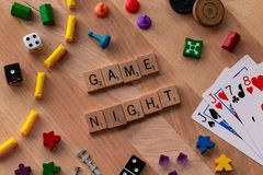 `Game Night` made from Scrabble game letters. Risk, Battleship pieces, Monopoly, Settler of Catan and other game pieces stock images