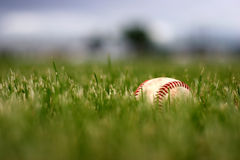 Game over. A used baseball, lost in the grass after the game Stock Photo