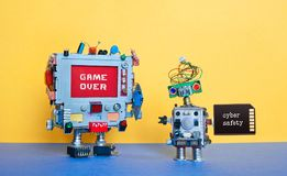 Game over cyber safety concept. Creative design robotic toys on blue ground yellow wall. Monitor computer pixel warning stock photo