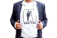 The game is over! newlywed in dark blue costume with opened shirt showing t-shirt with funny picture of marrieds. Indoor studio shot isolated on white royalty free stock image