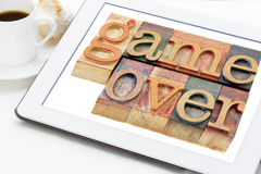 Game over in wood type. Game over (loss or failure concept) - words in vintage wooden letterpress printing blocks on a digital tablet with cup of coffee royalty free stock images