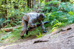 Game In A Paintball. Paintball sport player in protective uniform and mask aiming and shooting with gun outdoors Royalty Free Stock Photos