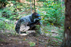Game In A Paintball. Paintball sport player in protective uniform and mask aiming and shooting with gun outdoors Stock Photography