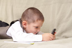 Game on phone. Photo of little boy laying on sofa and playing game on phone Stock Photo