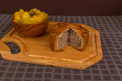 Game pie served with bowl of piccalilli Royalty Free Stock Image