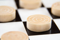 Game pieces on board. A board game with small wooden game pieces stock photography