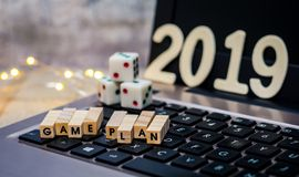 Game Plan 2019 still life concept with dice on laptop and fun lights on wooden board, shallow DOF. Game Plan still life concept with dice on laptop and fun stock photos