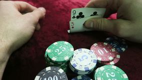 Game of poker. cards nine and seven. Man passes. lie around the chips. the game is on a red cloth velour table. stock video