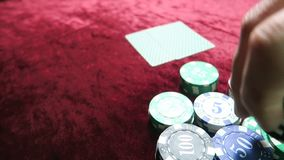 Game of poker. man makes a bet. lie around the chips. the game is on a red cloth velour table. stock video footage