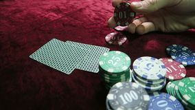Game of poker. recounting the chips in his hand. lie around the chips. the game is on a red cloth velour table. stock footage