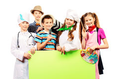 Game in professions. A group of children dressed in costumes of different professions holding white board. Isolated over white Stock Photography