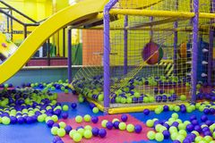 Game room. Large children`s playroom with a slide and colorful  balls in entertainment center, game room Stock Photo