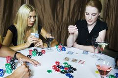 Game rush. Beautiful young woman with a tensioned expression looks at her cards under one of her oponent's suspicious looks, during a poker party Royalty Free Stock Image