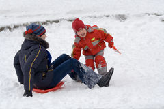 Game in snow. The little girl in red overalls plays with elder sister an ice slope Stock Photography