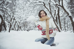 Game in snowballs. The girl sits on a lap in snow and throws in someone a snowball Royalty Free Stock Photo