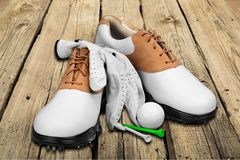 Pair of golfing shoes, ball and tees on wooden stock photo