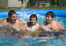 Game in swimming pool. Three brothers playing in the pool Stock Image
