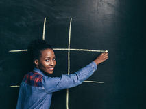 Game tic tac toe, afroamerican girl happy to play. Game tic tac toe, happy afroamerican girl draw white lines to play on wall blackboard. Fun, leisure, joy and Stock Images
