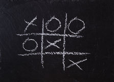 Game Tic Tac Toe on black slate board Stock Image