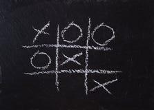 Game Tic Tac Toe on black slate board Stock Image