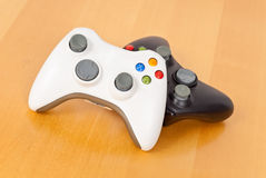 Game Time. Two video game controllers on wood Stock Photos