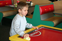 Game Time. A young boy plays table hockey Royalty Free Stock Photos