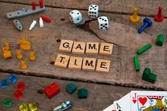 `Game Time` made from Scrabble game letters. Risk, Battleship pieces, Monopoly, Settler of Catan and other game pieces royalty free stock image