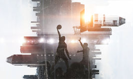 It is game time. Mixed media. Silhouettes of basketball players on modern city backgound. Mixed media Stock Photo